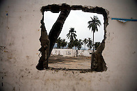 Palm trees are visible through a hole in the wall of a partially-demolished building in Sanya, Hainan, China.