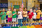 MR / Schenectady, NY. Zoller Elementary School. Kindergarten. Diverse group of students says the Pledge of Allegiance together as one child holds the flag. MR: AL-gKs. ID: AL-gKs. © Ellen B. Senisi
