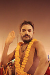 A Naga sadhu raises his right hand in blessing.