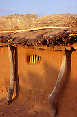 Dodoma, Tanzania. Thatched unpainted adobe house with window barred with rough sticks.