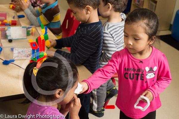 Education preschool 3-4 year olds girl helping sad friend blow her nose separation start of school year
