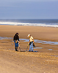 Two hunters cooperate to find their treasure on the beach at Rehoboth Beach, Delaware, USA.