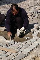 Operai mentre sistemano una strada lasticata in pietra. Workers  while settle a road paved in stone...