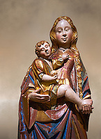 Gothic statue of The Virgin Mary (Madonna) holding the baby Jesus. Polychrome and gold leaf on wood by the Circle of Gil de Siloe around 1500, probably from Castella. Inv MNAC 64028. National Museum of Catalan Art (MNAC), Barcelona, Spain. Against a art background.
