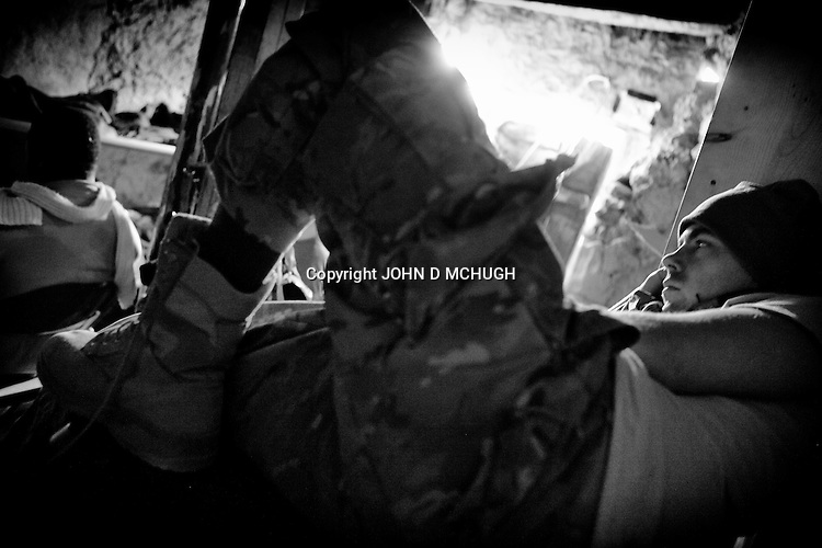 US soldiers from 2nd Platoon, 2/27 Infantry, 25 Infantry Division, watch a movie on a laptop at Checkpoint 2.5, beside Saw village, in Kunar province, 01 Dec 2011. (John D McHugh)