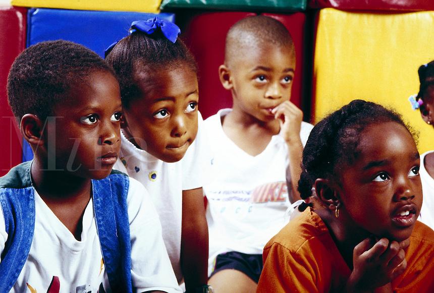 Wide-eyed children listening to teacher in school classroom. children, people. Birmingham Alabama United States.