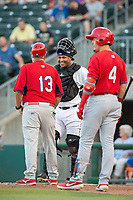 Northwest Arkansas Naturals catcher Meibrys Viloria (22) (center) laughs with Springfield Cardinals manager Joe Kruzel (13) while umpires review a call on Springfield Cardinals infielder Evan Mendoza (4) (right) on May 16, 2019, at Arvest Ballpark in Springdale, Arkansas. (Jason Ivester/Four Seam Images)