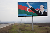 Azerbaijan. Oguz region. 20 km from Oguzi. An empty concrete road and a huge poster of the current President of Azerbaijan, Ilham  Aliyev (born December 24, 1961), who is the son of of the deceased political leader Heydar Aliyev. Ilham  Aliyev also functions as the head of the New Azerbaijan Party. The azeri flag is a national symbol and consists of three equal horizontal bands, blue, red, and green; a white crescent and an eight-pointed star (Rub El Hizb) are centered in the red band. The eight points of the star stand for the eight branches of the Turkic people. The blue band is the color of the Turks, the green is for Islam and red is for progress. © 2007 Didier Ruef