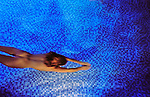 young woman swims naked underwater in pool above blue tiles sidelighting and shadows