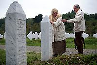 Rabija (left) and Munib Hodzic at the graveside of their only child Sabahudin buried at the cemetery for the victims of the Srebrenica massacre in Potocari. Sabahudin was one of 8,000 mainly Bosnian Muslim men and boys murdered by Bosnian Serb forces led by former general Ratko Mladic. His body lay in an unknown mass grave for 14 years following the genocide before being discovered and laid to rest in Potocari..Mladic is one of the most sought after suspects from the Bosnian conflict. He has been indicted by the UN war crimes tribunal on charges of genocide and crimes against humanity..