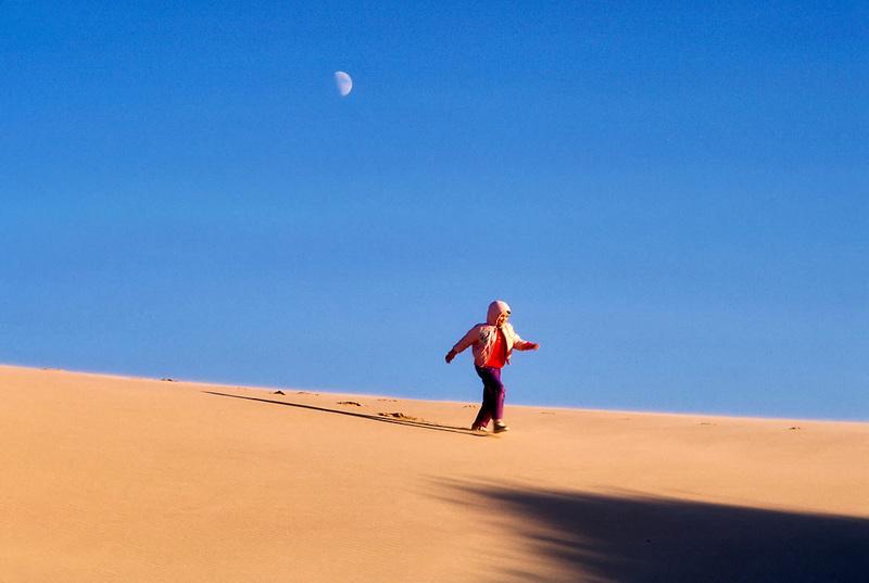 Child running down sand dune. Near Florence, Oregon.