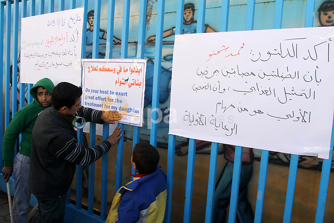 Palestinian students take part in a protest in front of the headquarters of the United Nations (UNRWA) solidarity with the twins suffering from metabolic disorder, against the medical negligence for lack of early detection of their disease in Gaza City on December, 18, 2013. Photo by Mohammed Asad