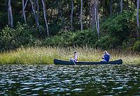 Senior couple navigate enjoy the view from a coanoe, Cape Cod, Massachusetts, USA
