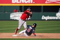 Boston Red Sox shortstop Jonathan Araúz (3) throws to first base as Ryan Goins (8) slides in during a Major League Spring Training game against the Atlanta Braves on March 7, 2021 at CoolToday Park in North Port, Florida.  (Mike Janes/Four Seam Images)