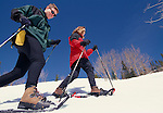 A close-up of a couple snowshoeing across the side of a hill in the Rocky Mountains of Colorado