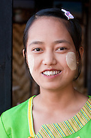 Myanmar, Burma.  Young Burmese Woman of Intha Ethnic Group, Waitress in a Restaurant Serving Tourists.  Inle Lake, Shan State.  She is wearing thanaka paste on her cheeks, a cosmetic sunscreen.