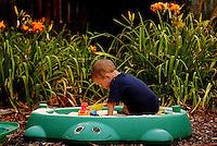 A toddler enjoys his afternoon sifting sand in his backyard sandbox.