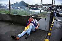 CALARCA - COLOMBIA, 30-04-2021: Un manifestante se resguarda mientras mitiga el efecto del gas lacrimógeno lanzado por la policía antidisturbios a la salida de Calarcá en la vía que conduce al alto de La Línea durante el tercer día de Paro Nacional en Colombia hoy, 30 abril de 2021, y que comenzó el pasado 28 de abril de 2021 para protestar por la reforma tributaria que adelanta el gobierno de Ivan Duque además de la precaria situación social y económica que vive Colombia. El paro fue convocado por sindicatos, organizaciones sociales, estudiantes y la oposición. / A protester takes cover while mitigating the effect of tear gas fired by riot police at the exit of Calarcá on the road that leads to the top of La Línea during the third day of the National Strike in Colombia today, April 30, 2021, and which began on April 28, 2021 to protest the tax reform that the government of Ivan Duque is also advancing of the precarious social and economic situation that Colombia is experiencing. The strike was called by unions, social organizations, students and the opposition in Colombia. Photo: VizzorImage / Santiago Castro / Cont