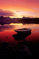 A ROW BOAT silhouetted against the magnificent colors of SUNRISE - BLUE MOOSE COVE, GLACIER BAY NATIONAL PARK, ALASKA