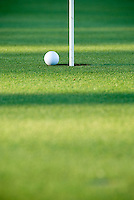 White golf ball at edge of cup with flag in hole