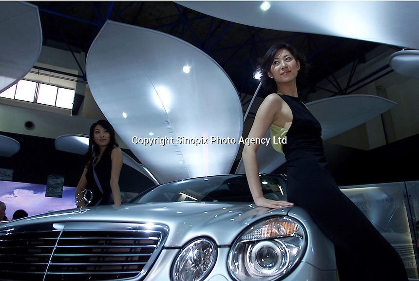 "A Mercedes-Benz car flanked by two models at a car show in Beijing, ""Auto China 2000""."
