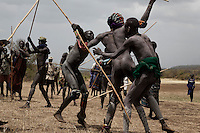 Bugu has a dispute over a woman and challenges his rival to a Donga (stick fight).  When the fighting actually begins there is ritualized posturing that culminates with two men beating the crap out of each other by wailing on their opponents with their long penis shaped sticks.