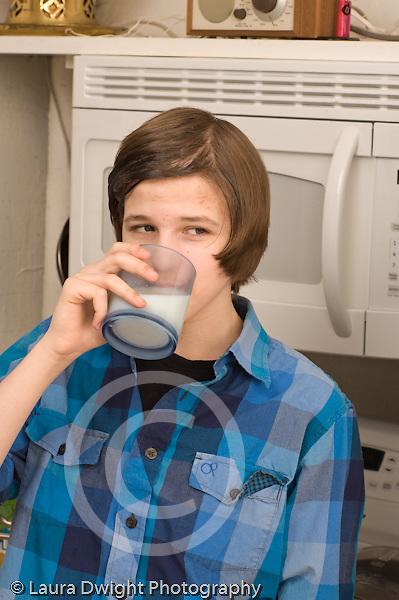 Teenage boy at home in kitchen drinking beverage glass of milk age 14