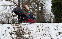 A mother prepares to push her children down the hill while sledging following snowfall at Foots Cray Meadow, Sidcup, Kent, England on the 9 February 2021. Photo by Alan Stanford.