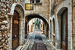 "Early morning shot of an archway and street (the Rue Grande) in Saint Paul de Vence. Over the arch is the ""pontis"", or bridgework, connecting buildings on opposite sides of the street."