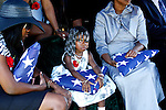 Janye M. Clay, two years old, sitting in between her mother (left) Jasmine Taylor-Clay her grandmother Georgetta Jennings, clenches the American flag given to her to honor her father Staff Sgt. Jamal Clay. Justin A. Shaw - photographer.