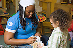 Preschool classroom 3-4 year olds college age female volunteer working with children in classroom