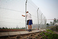 """CHINA. Beijing. An old man peers through a fence, trying to catch a glimpse of the new Olympic park. In recent years construction has boomed in Beijing as a result of the country's widespread economic growth and the awarding of the 2008 Summer Olympics to the city. For Beijing's residents however, it seems as their city is continually under construction with old neighborhoods regularly being razed and new apartments, office blocks and sports venues appearing in their place. A new Beijing has been promised to the people to act as a showcase to the world for the 'new' China. Beijing's residents have been waiting for this promised change for years and are still waiting, asking the question """"Where's the new Beijing?!"""". 2008."""