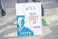 """A crowd gathers in Boston Common for the 2020 Women's March protest in opposition to the re-election of US president Donald Trump in Boston, Massachusetts, on Sat., Oct. 17, 2020.<br /> The sign here features an image of Democratic presidential nominee Joe Biden and reads """"Will you shut up, man?"""" a quote from Biden during the first presidential debate with US President Donald Trump."""