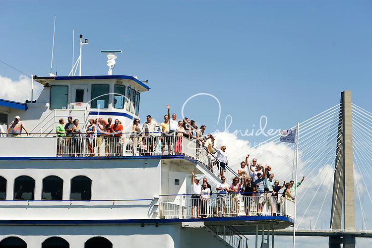 A group of tourists wave from their sight seeing boat in Charleston, SC.