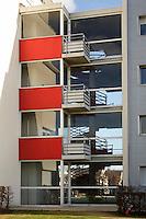 Escalier interieur derriere une facade vitree avec avec plateformes d'evacuation exterieures