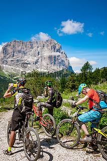 Italien, Suedtirol (Trentino - Alto Adige), Dolomiten: kurze Rast unterhalb des Groednerjoch, im Hintergrund der Langkofel | Italy, South Tyrol (Trentino - Alto Adige), Dolomites: mountainbiker having a short break near Gardena Pass (Passo Gardena), Sassolungo mountain at background