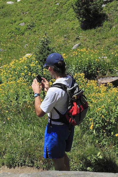 Man using smart phone in Indian Peaks Wilderness Area, west of Boulder, Colorado.