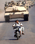 Iraqi civilians on motorcycle weaves in and out of a Task Force 3-67 presence patrol in Khalis, Iraq on May 8, 2003.  (photo by Khampha Bouaphanh)
