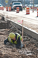 A worker checks the level of fill dirt used to build temporary ramps as a sheet of steel is laid for the ramp into a shopping center after new concrete curbs were laid on Westerville Road at Dempsey as roadway improvements near completion at the intersection. The changes are part of an improvement project at the I-270 interchange to upgrade the entrance road to Westerville, OH.