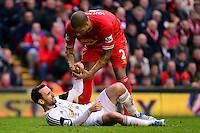Sunday, 23 February 2014<br /> Pictured: Liverpool's Glen Johnson helps Swansea City's Leon Britton back to his feet<br /> Re: Barclay's Premier League, Liverpool FC v Swansea City FC v at Anfield Stadium, Liverpool Merseyside, UK.