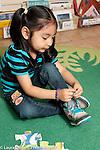 Education preschool 3-4 year olds girl tying her shoe