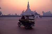 Early morning in Vientiane 1992,the movement of the local transportation, a tricicle at the center of town