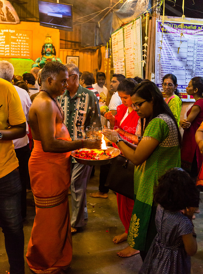 Hindu Priest with Worshiper Performing Ritual of Touching the Lamp, Sree Veera Hanuman Hindu Temple, Kuala Lumpur, Malaysia.