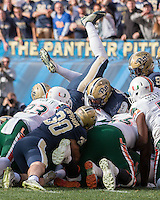 The Pitt defense lead by Matt Galambos (legs in air) and Mike Caprara (30) unsuccessfully prevent a Miami quarterback sneak for a touchdown  by The Miami Hurricanes quarterback Brad Kaaya. football team defeated the Pitt Panthers 29-24 on  Friday, November 27, 2015 at Heinz Field, Pittsburgh, Pennsylvania.