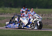 Apr. 26, 2013; Baytown, TX, USA: NHRA pro stock motorcycle rider Adam Arana (right) and father Hector Arana Sr are being pushed by a crew member on the return road back to the pits during qualifying for the Spring Nationals at Royal Purple Raceway. Mandatory Credit: Mark J. Rebilas-