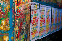 "Just-finished music party posters are seen drying on the scribbled wall in the sign painting workshop in Cartagena, Colombia, 14 April 2018. Hidden in the dark, narrow alleys of Bazurto market, a group of dozen young men gathered around José Corredor (""Runner""), the master painter, produce every day hundreds of hand-painted posters. Although the vast majority of the production is designed for a cheap visual promotion of popular Champeta music parties, held every weekend around the city, Runner and his apprentices also create other graphic design artworks, based on brush lettering technique. Using simple brushes and bright paints, the artisanal workshop keeps the traditional sign painting art alive."