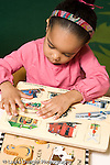 Education Preschool 3-5 year olds girl stting at table playing with wooden puzzle vertical