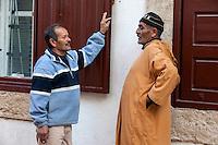 Essaouira, Morocco.  Two Men in Conversation, Sidi Mohammed ben Abdallah Street Scene.