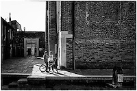 Two young boys, one on a bicycle, both hiding their faces from the camera, in Venice, Italy.