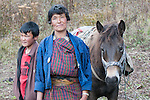After a day with her yak herd, this woman and her son arrive home to their tent to start the evening chores. (Punakha, Bhutan)